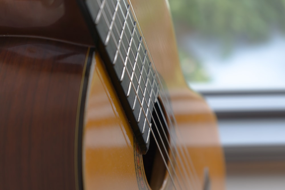 brown acoustic guitar in close up photography
