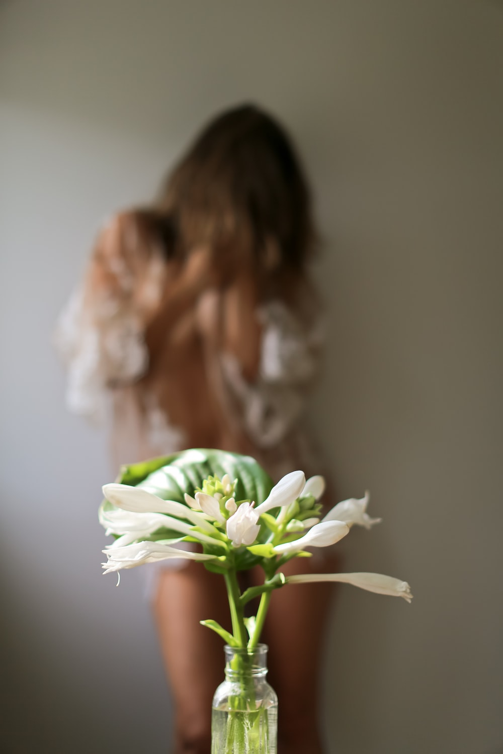 woman holding white flower in close up photography