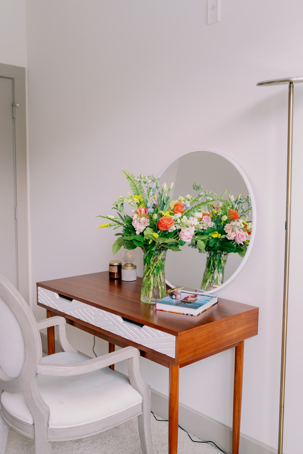 white and red flowers in clear glass vase on brown wooden table