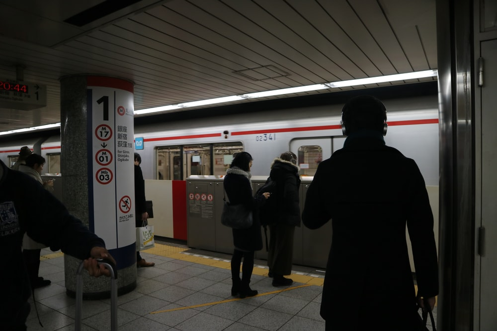man in black coat standing near red train