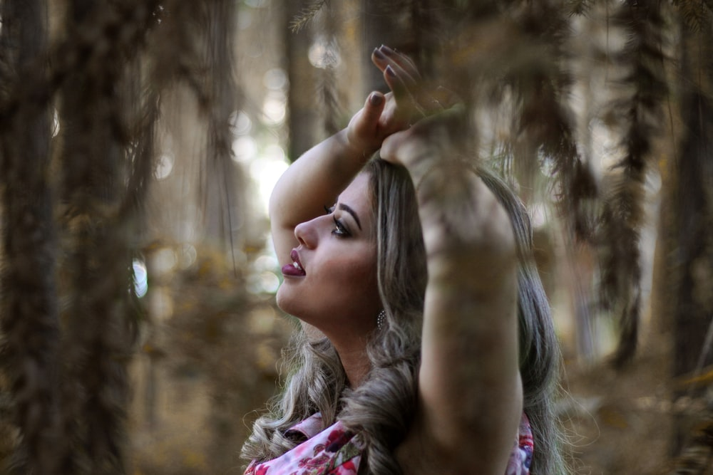 girl in pink and white floral shirt standing near brown trees during daytime