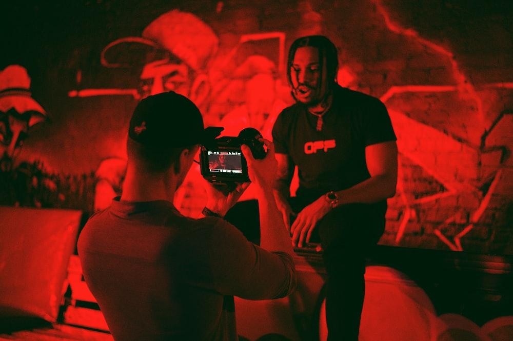 man in black crew neck t-shirt holding black smartphone