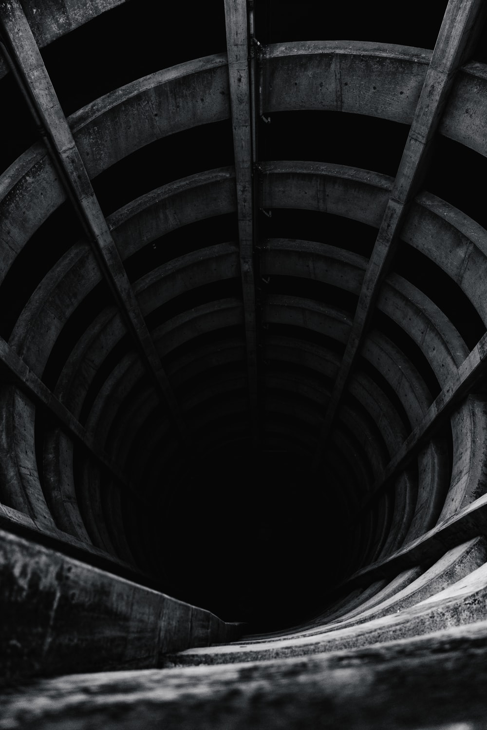 grayscale photo of wooden tunnel