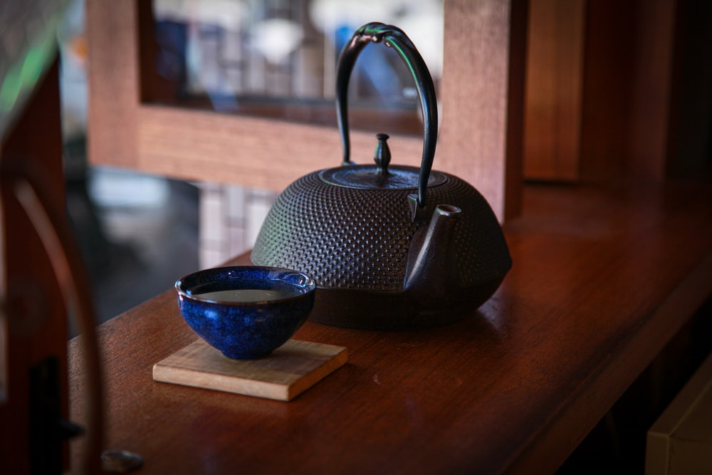 black teapot on brown wooden table