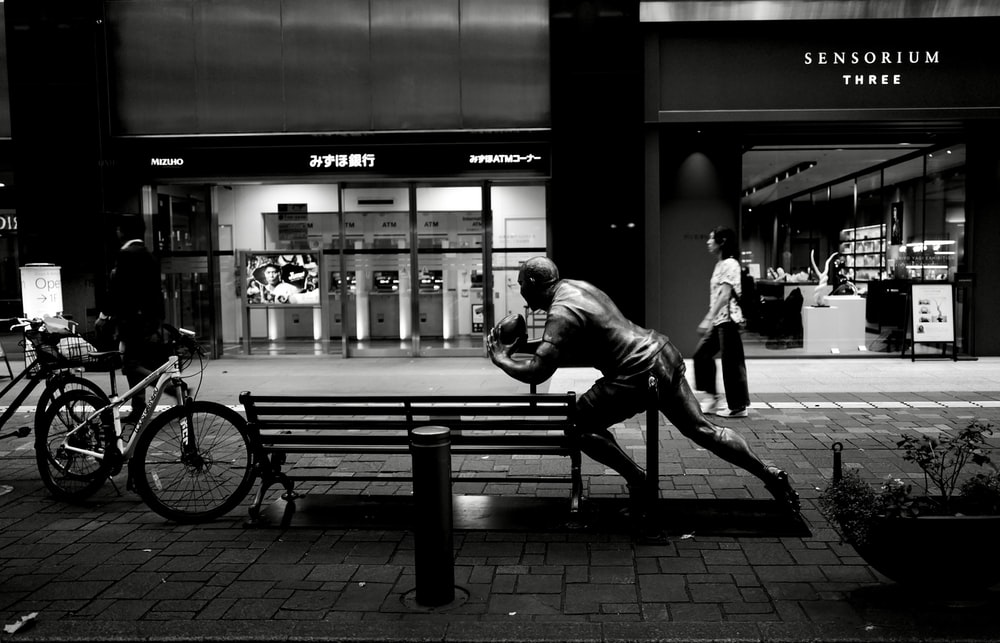 grayscale photo of man sitting on bench near building