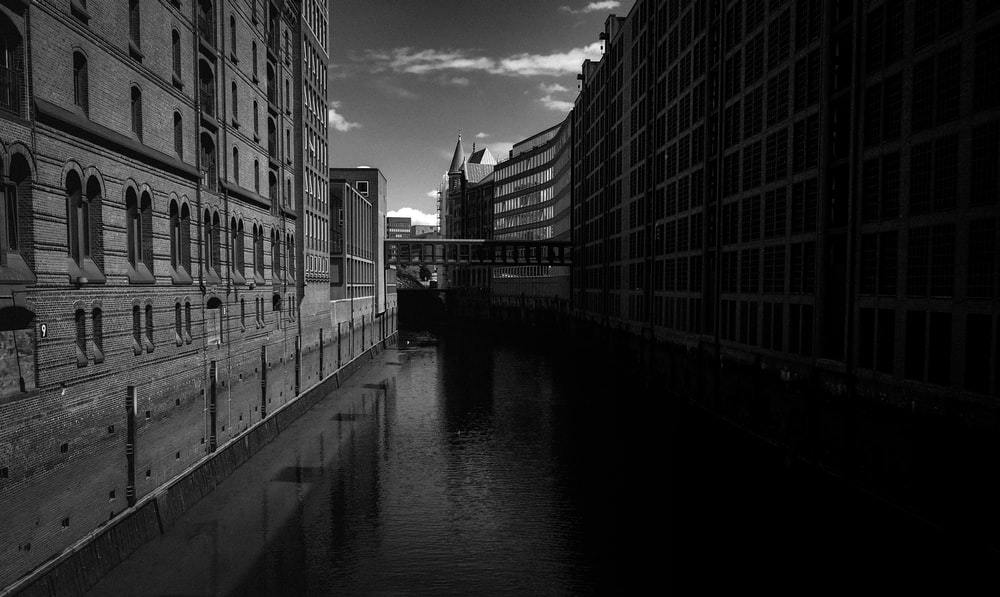 grayscale photo of river between buildings