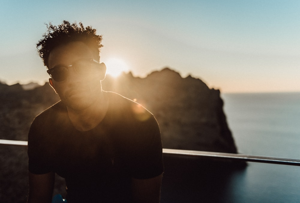 man in black crew neck t-shirt standing near body of water during sunset