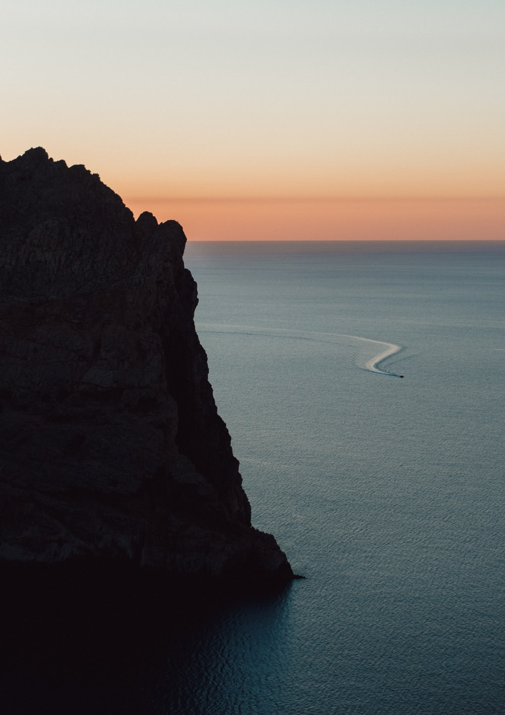 white sailboat on sea near brown rock formation during daytime