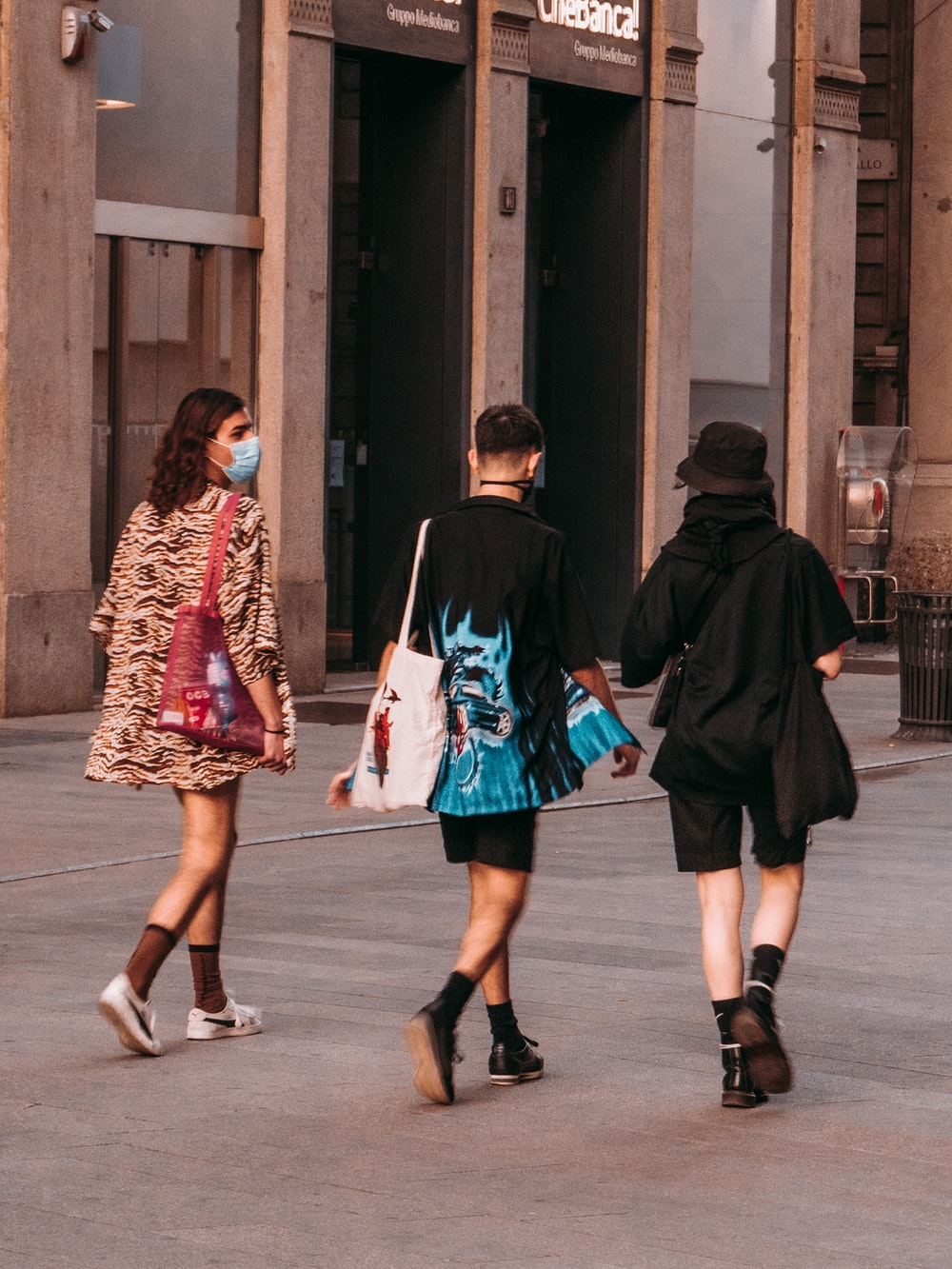 2 girls in green and black dress walking on sidewalk during daytime