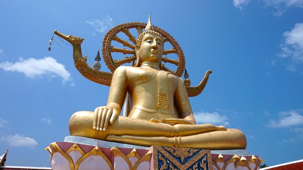 gold buddha statue under blue sky during daytime