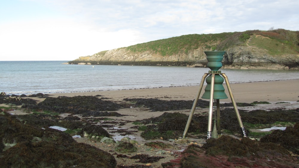 green and gray metal stand on seashore during daytime