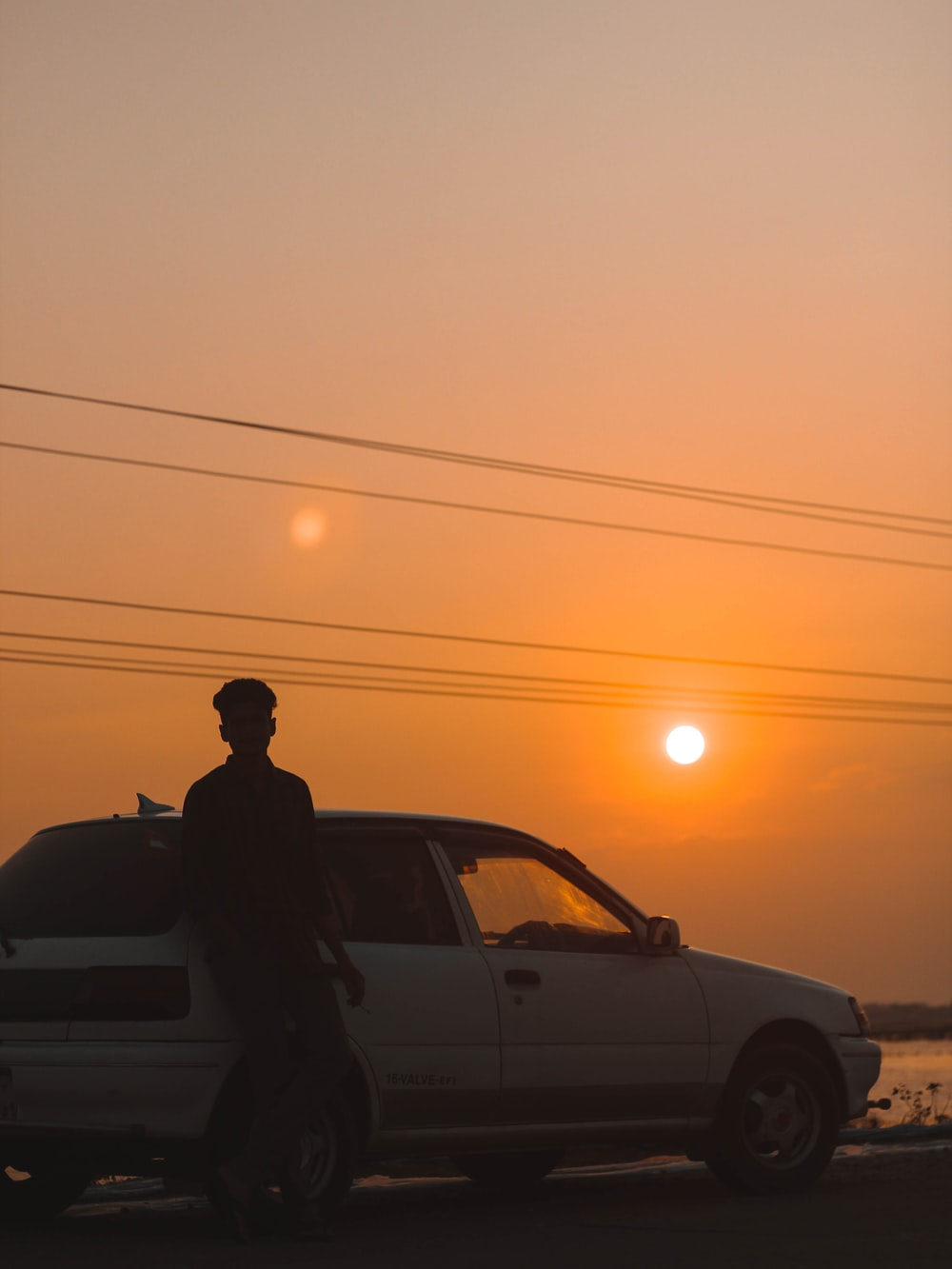 silhouette of man standing beside car during sunset