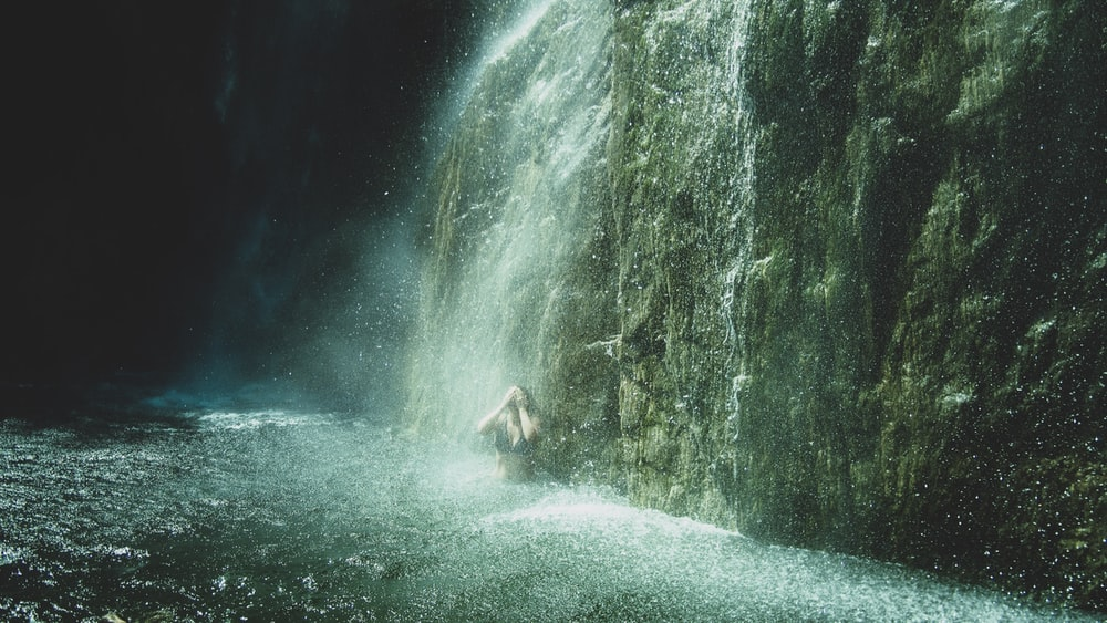 person in white shirt and black shorts standing on water falls during daytime