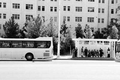 grayscale photo of white bus on road turkmenistan zoom background