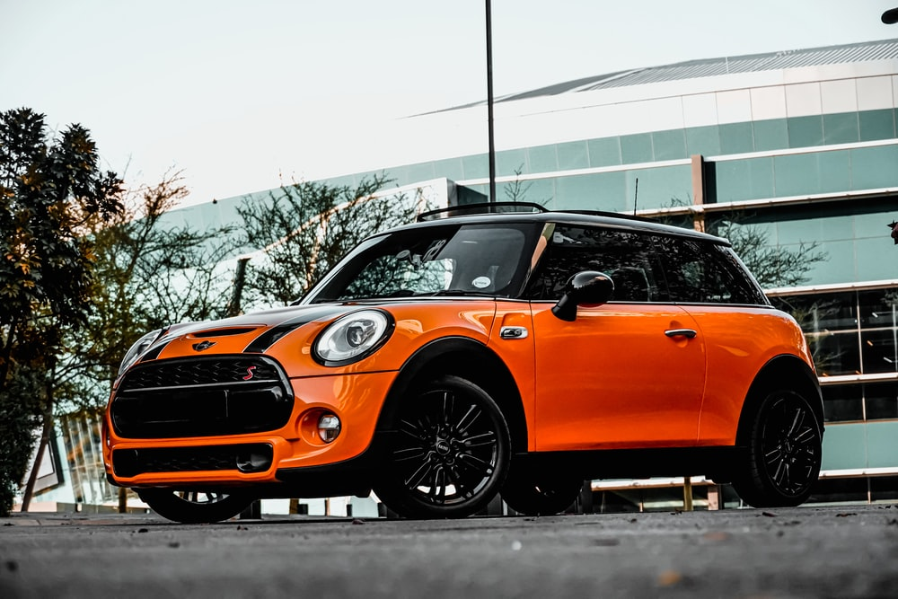 orange car on gray asphalt road during daytime