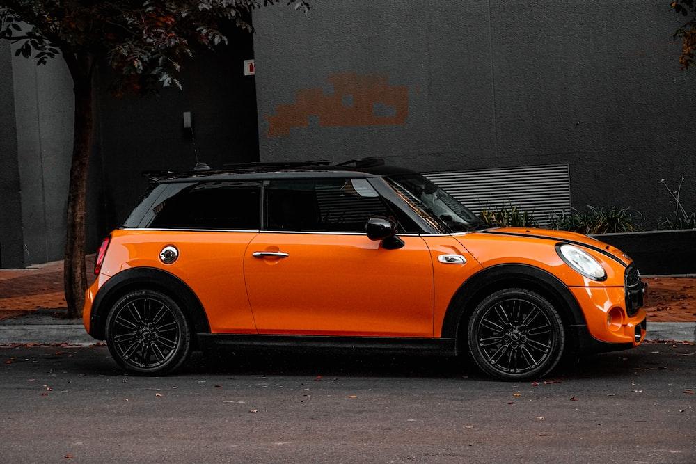 orange car parked beside gray wall