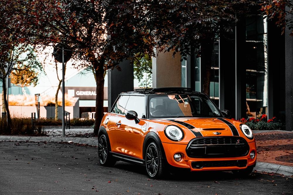 orange bmw m 3 parked on sidewalk during daytime