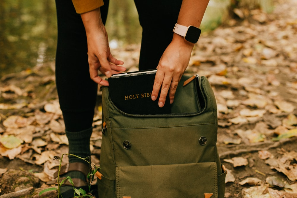 person holding green and black backpack