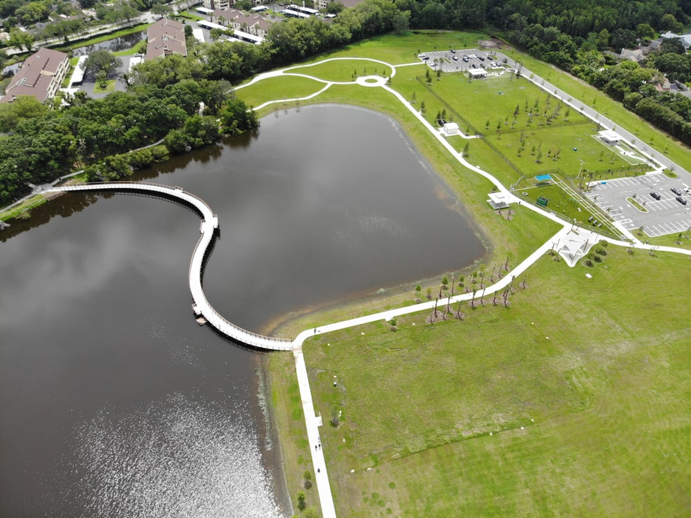 aerial view of river in the middle of green grass field