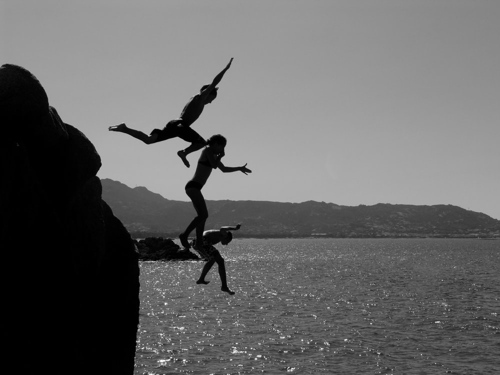 grayscale photo of 2 men jumping on water