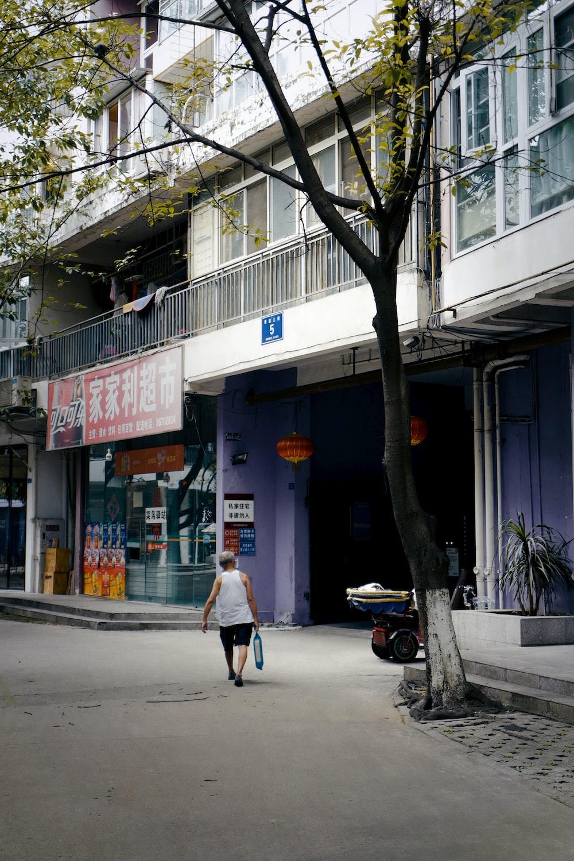 woman in white coat walking on sidewalk during daytime