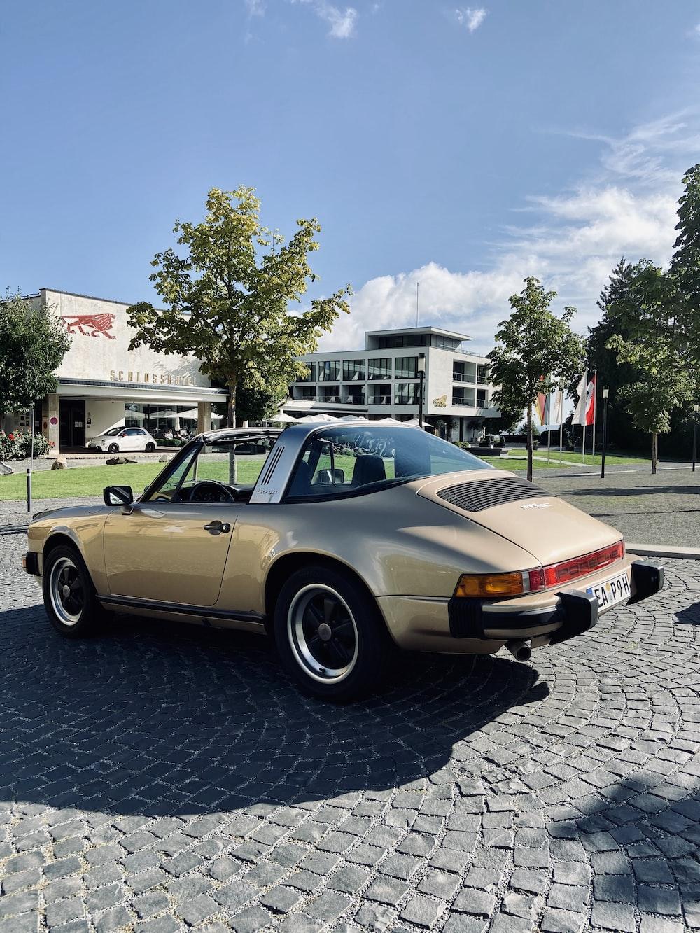 gold chevrolet camaro parked on street during daytime