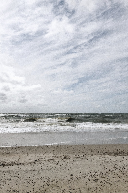sea waves crashing on shore under white clouds during daytime