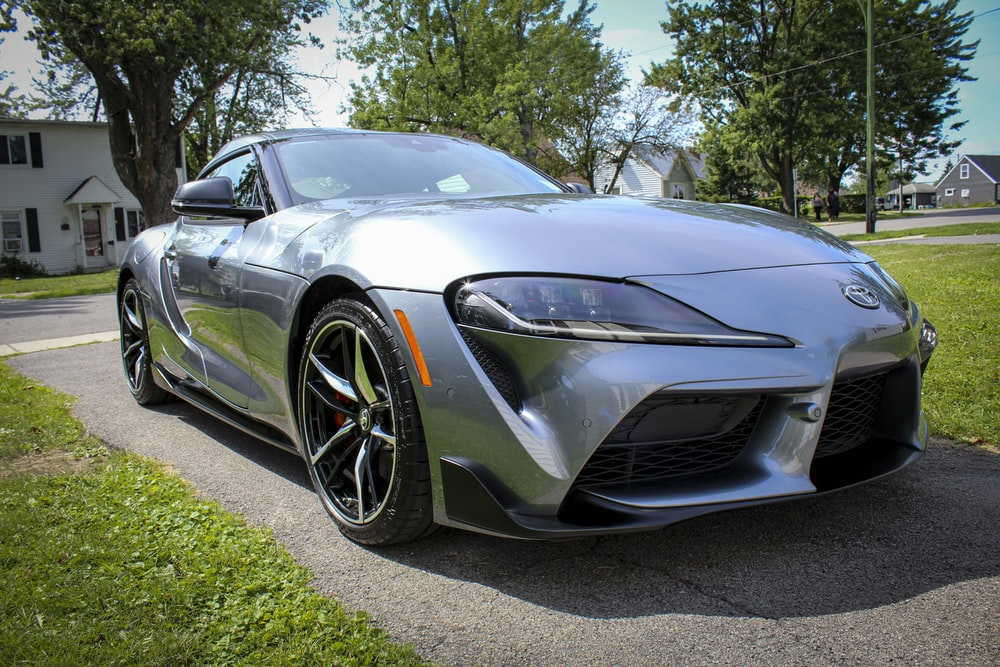 silver mercedes benz coupe parked on green grass field during daytime