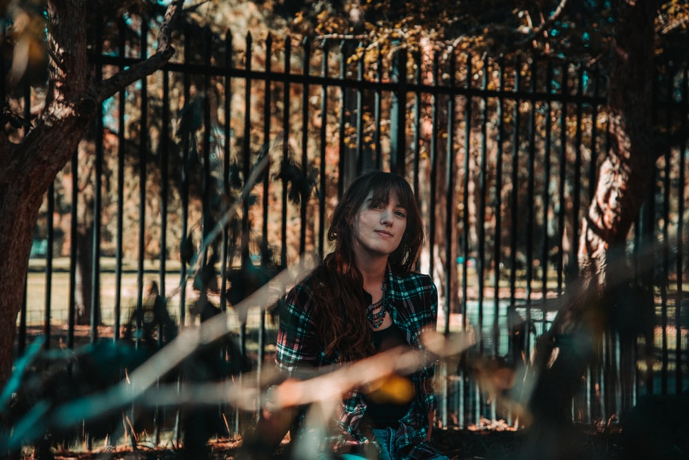 woman in black and red plaid dress shirt standing beside black metal fence during daytime