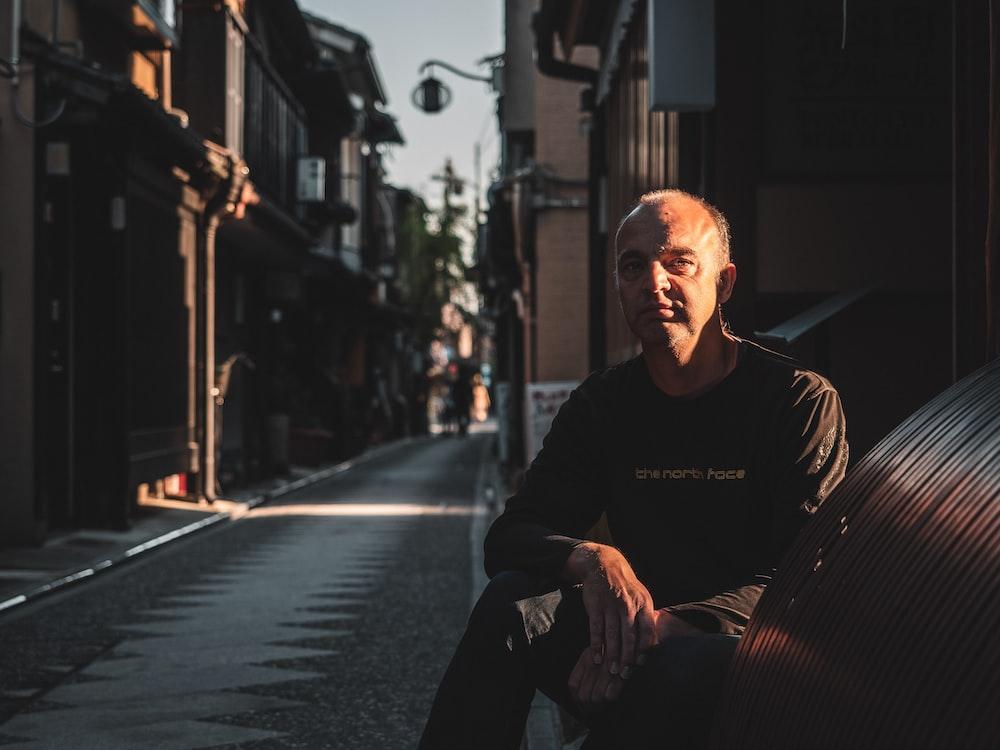 man in black hoodie sitting on sidewalk during daytime