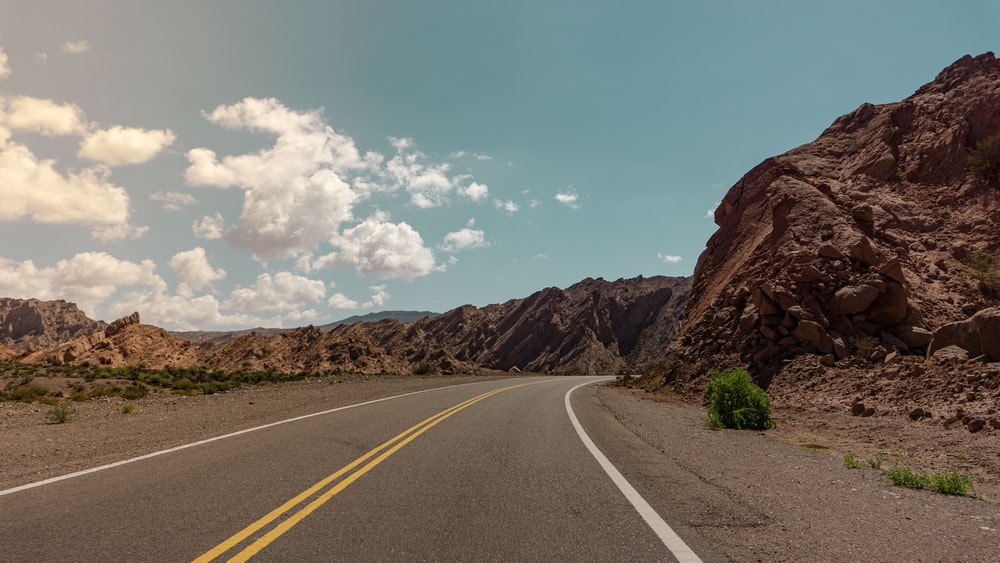 gray concrete road near brown rocky mountain under blue sky during daytime