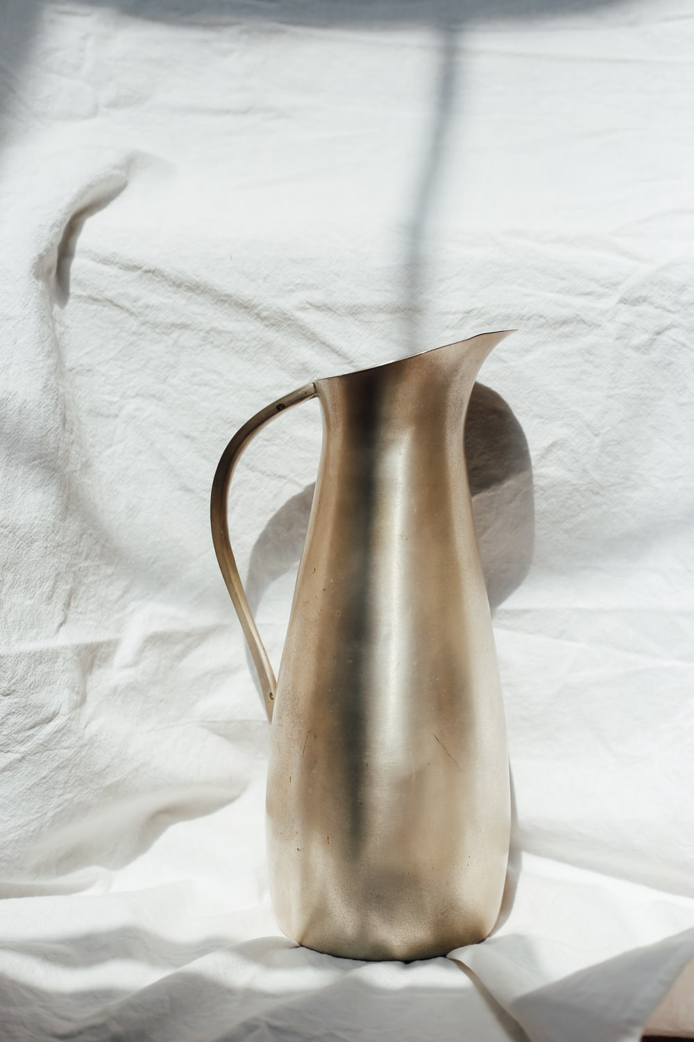 stainless steel pitcher on white textile