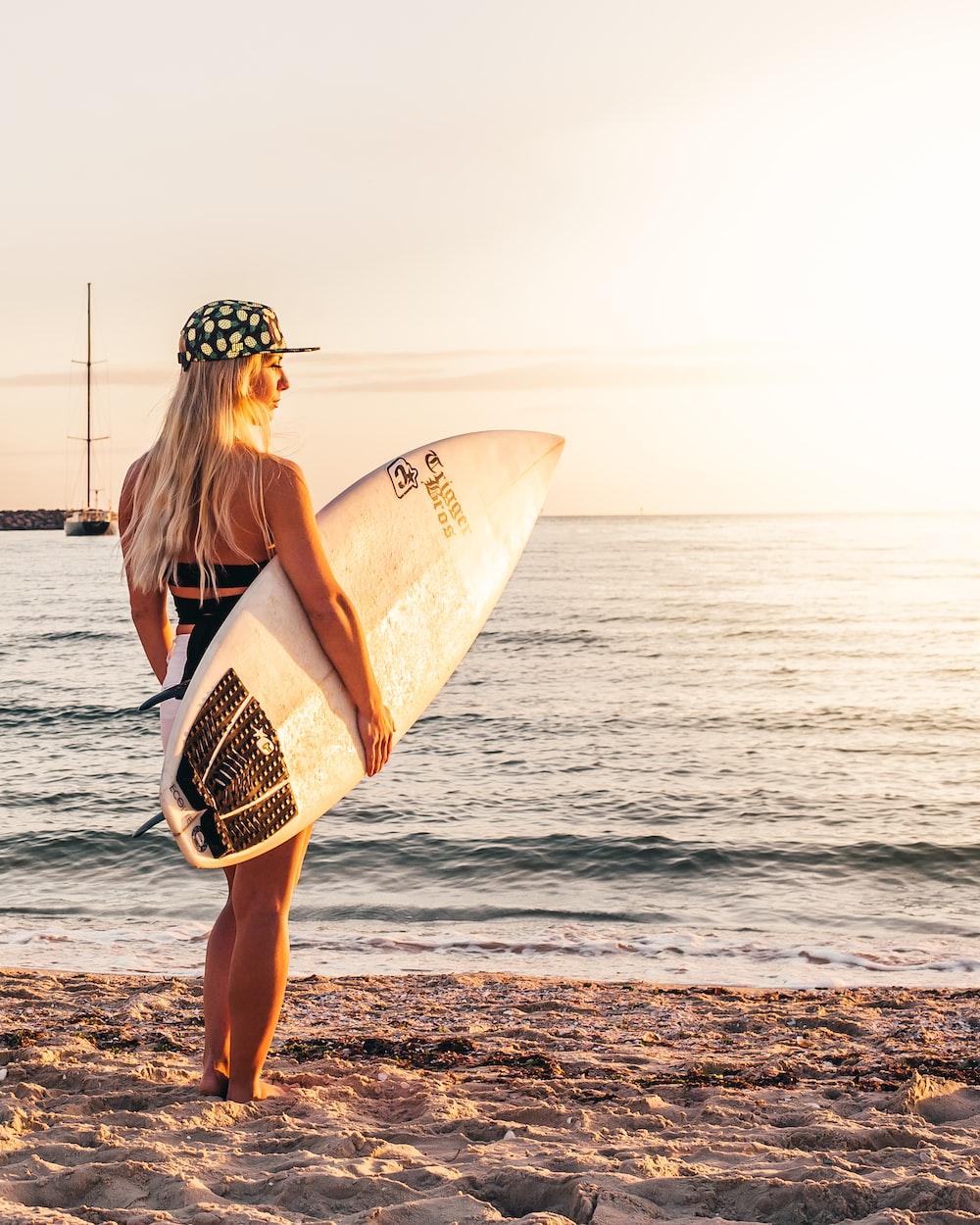 woman in black bikini holding surfboard standing on beach during daytime