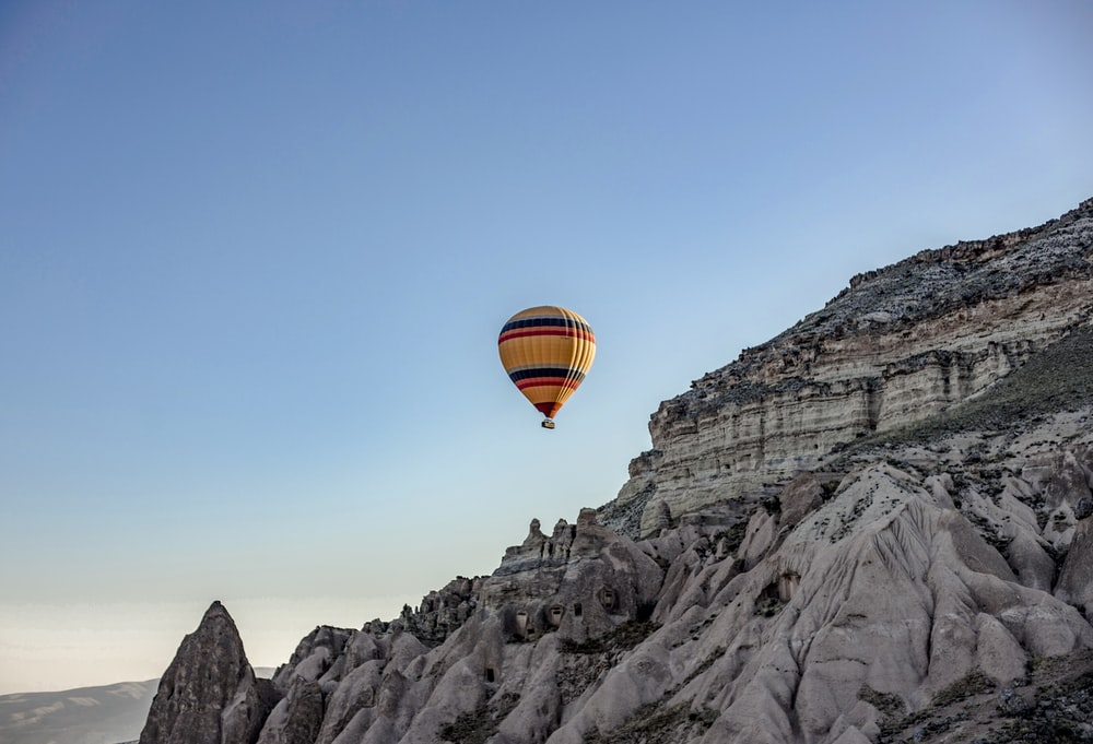 hot air balloon flying over rocky mountain during daytime