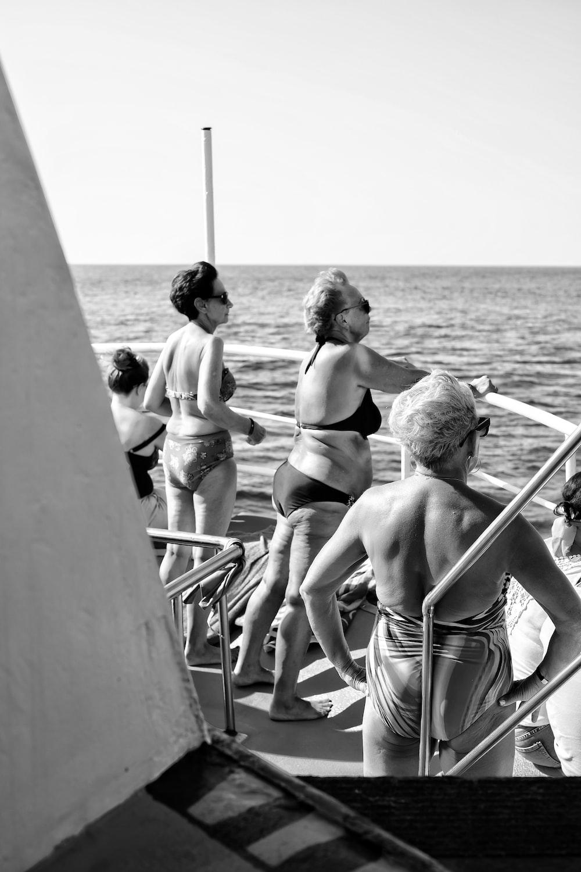 grayscale photo of 3 women in bikini standing on beach