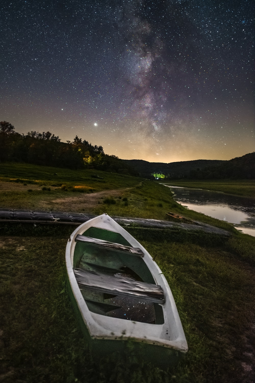 white canoe on green grass field near lake during night time
