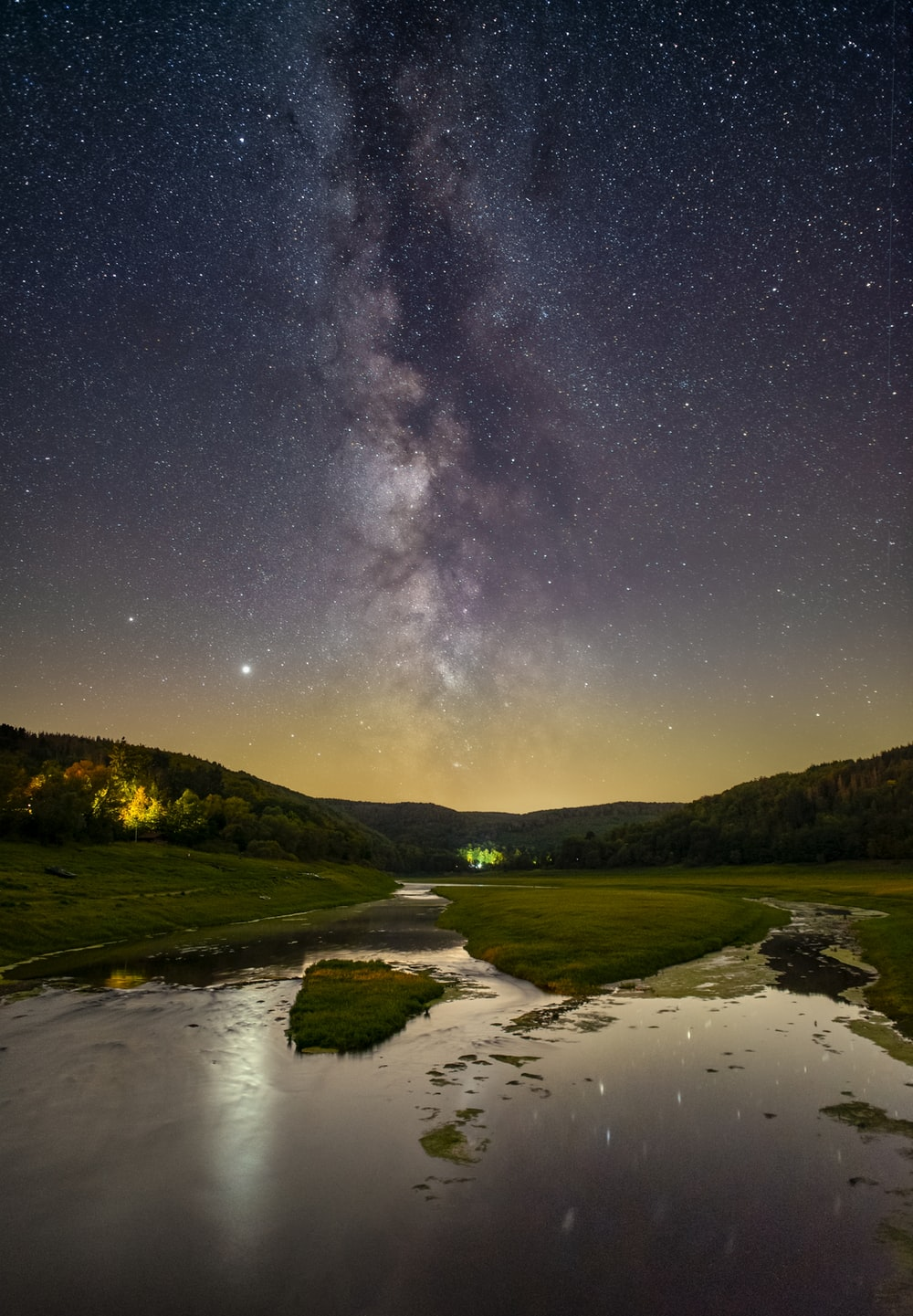 lake in the middle of green grass field under starry night