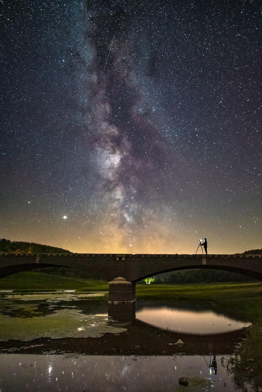 man standing on bridge under starry night