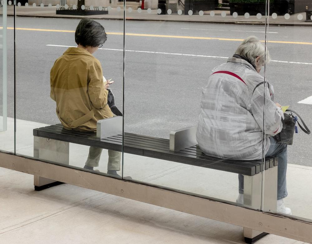woman in gray jacket standing beside glass window