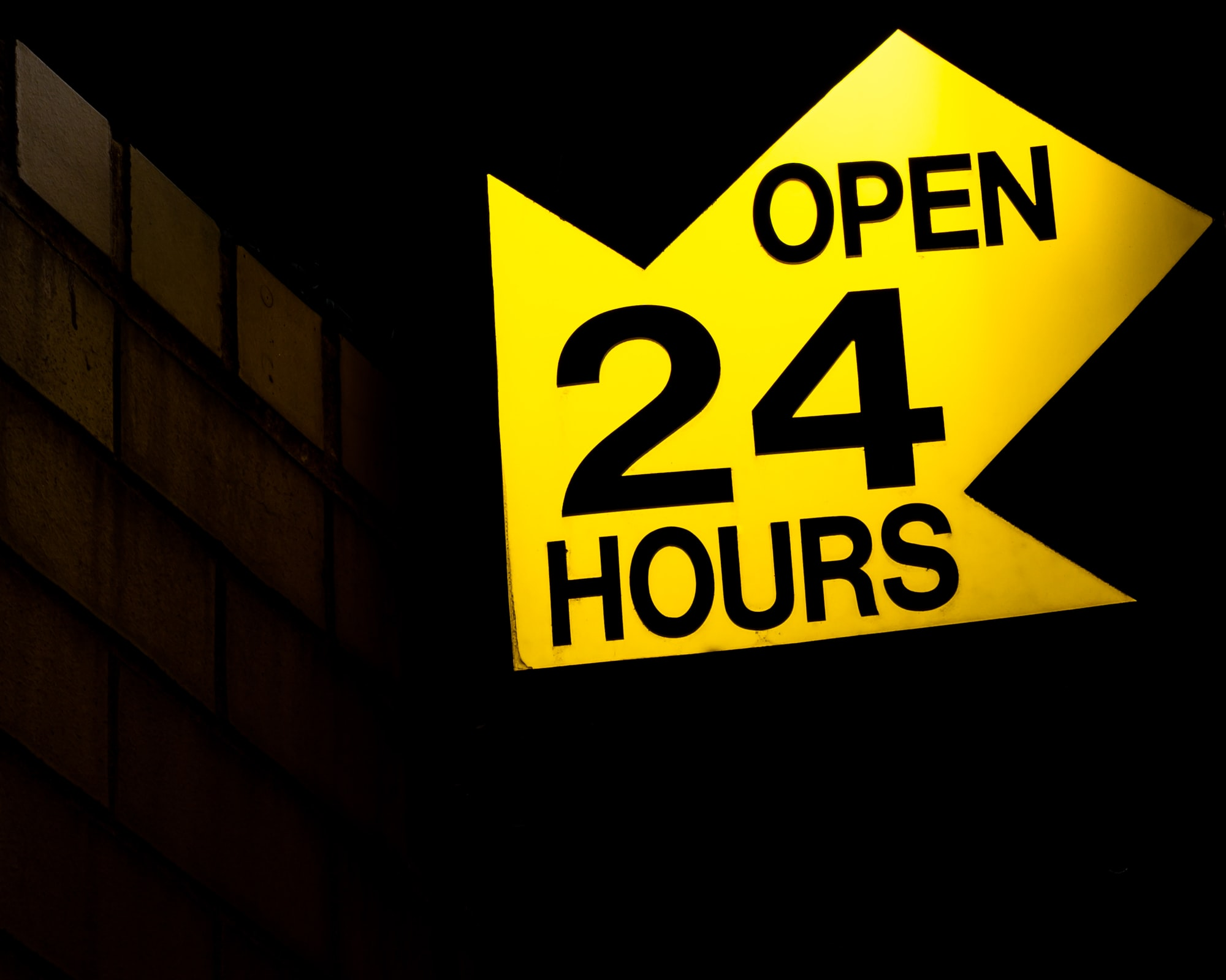 Yellow arrow shaped sign that reads open 24 hours.