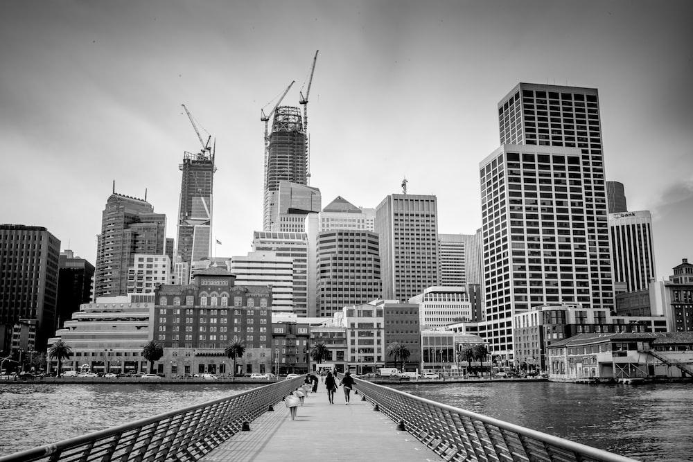 grayscale photo of people walking on sidewalk near city buildings