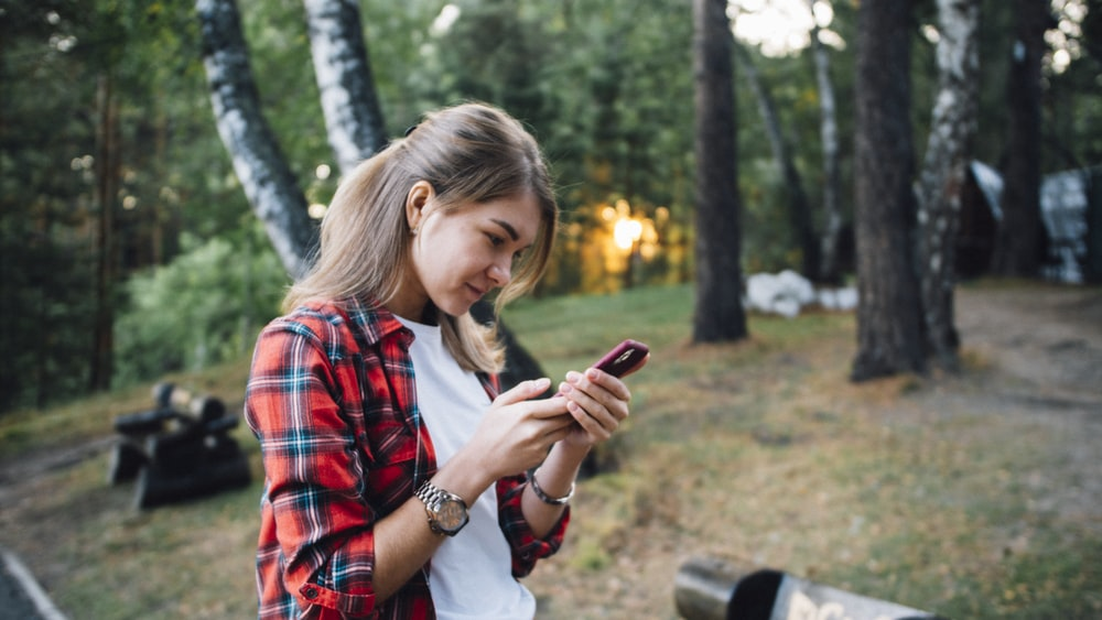 girl in red and black plaid button up shirt holding smartphone