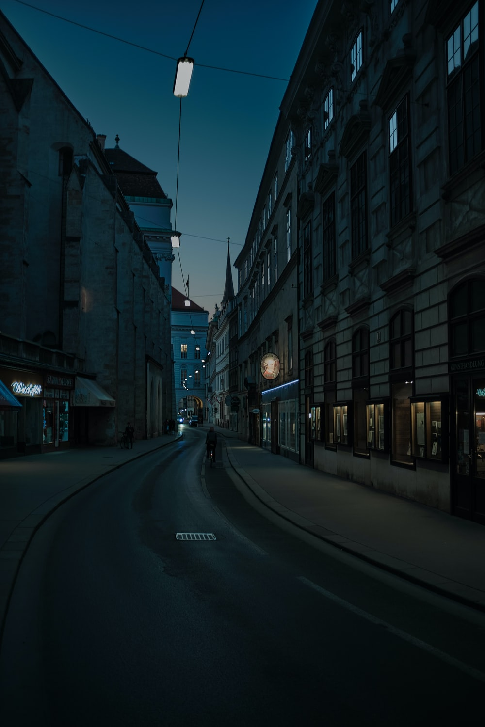 empty road between high rise buildings during night time