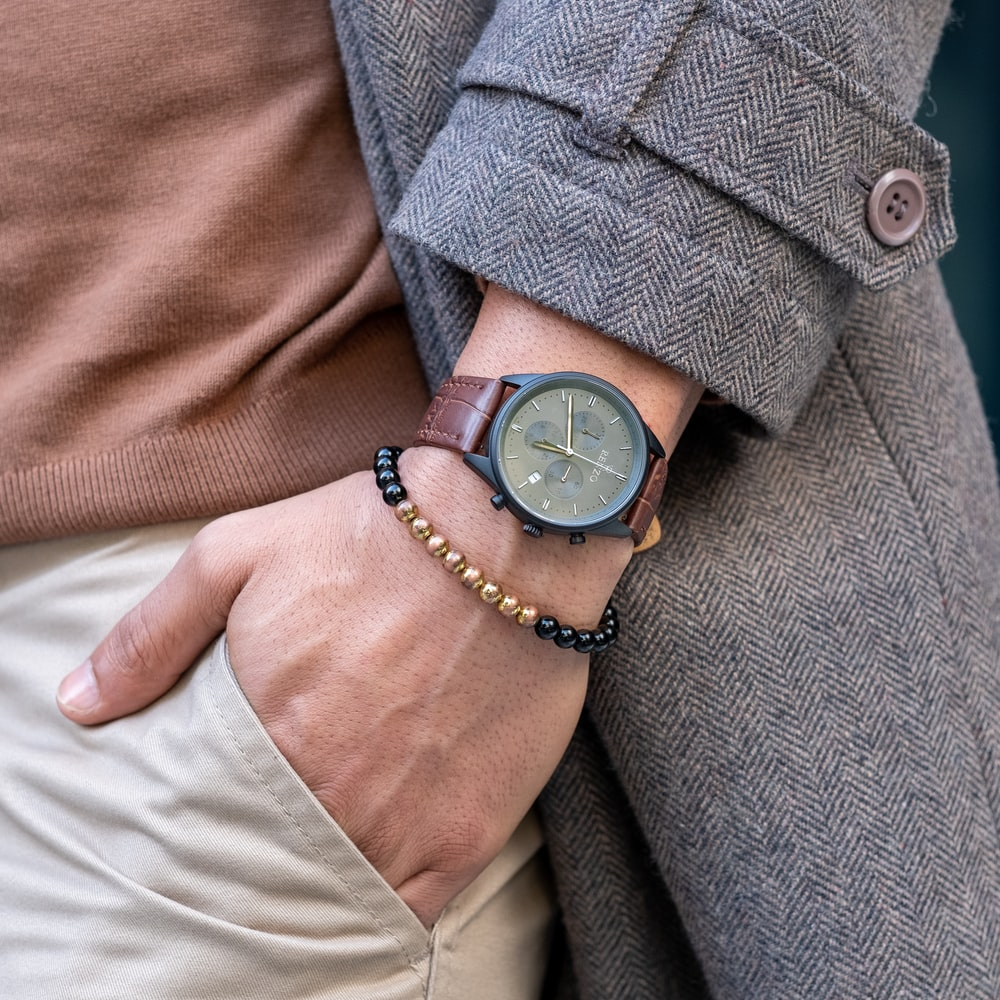 person wearing black leather strap analog watch