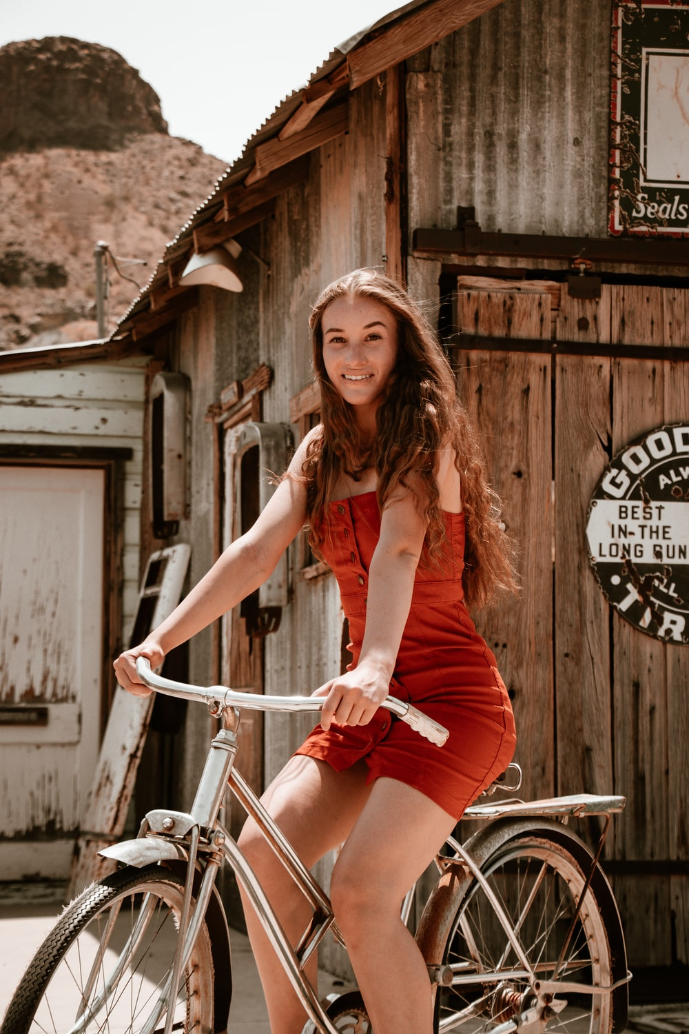 woman in red sleeveless dress sitting on white bicycle