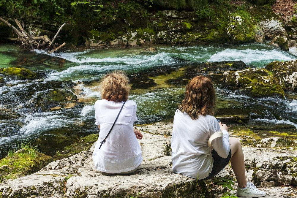 2 women sitting on rock near river during daytime