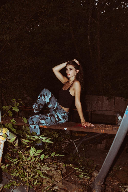 woman in black tank top and blue pants sitting on brown wooden bridge