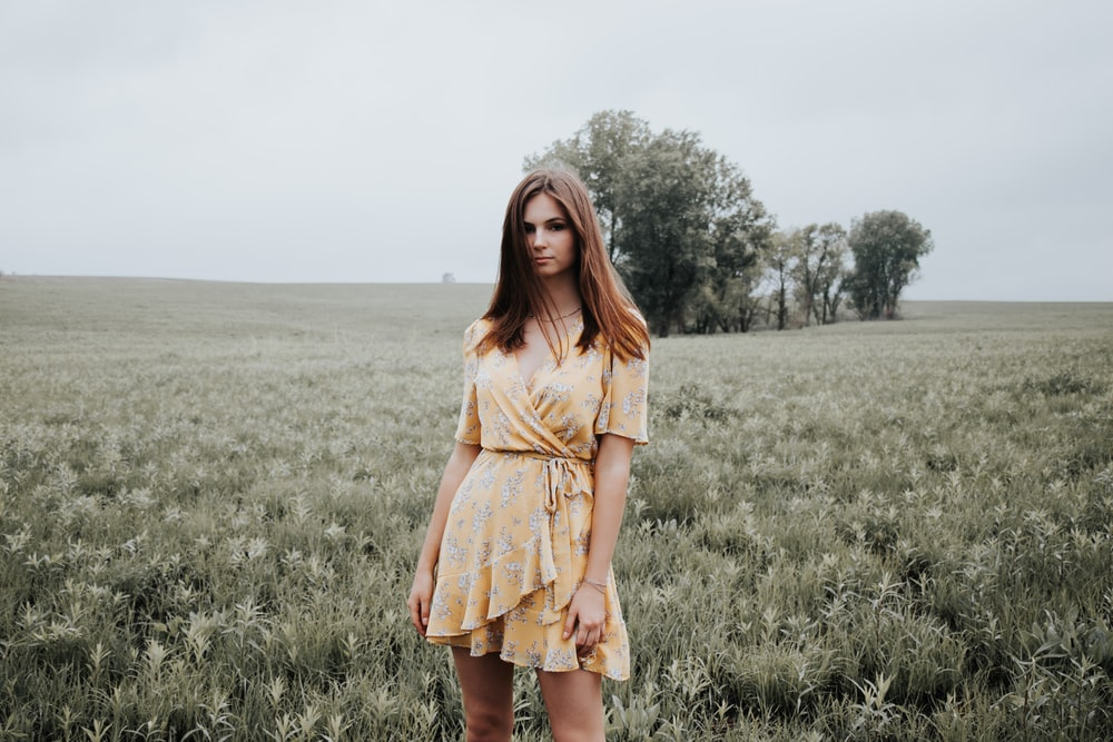 woman in yellow dress standing on green grass field during daytime