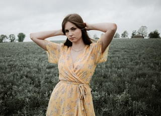 woman in yellow floral dress standing on green grass field during daytime