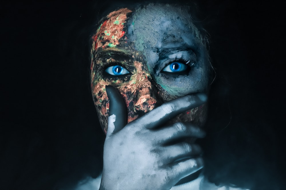 person with face paint in black background